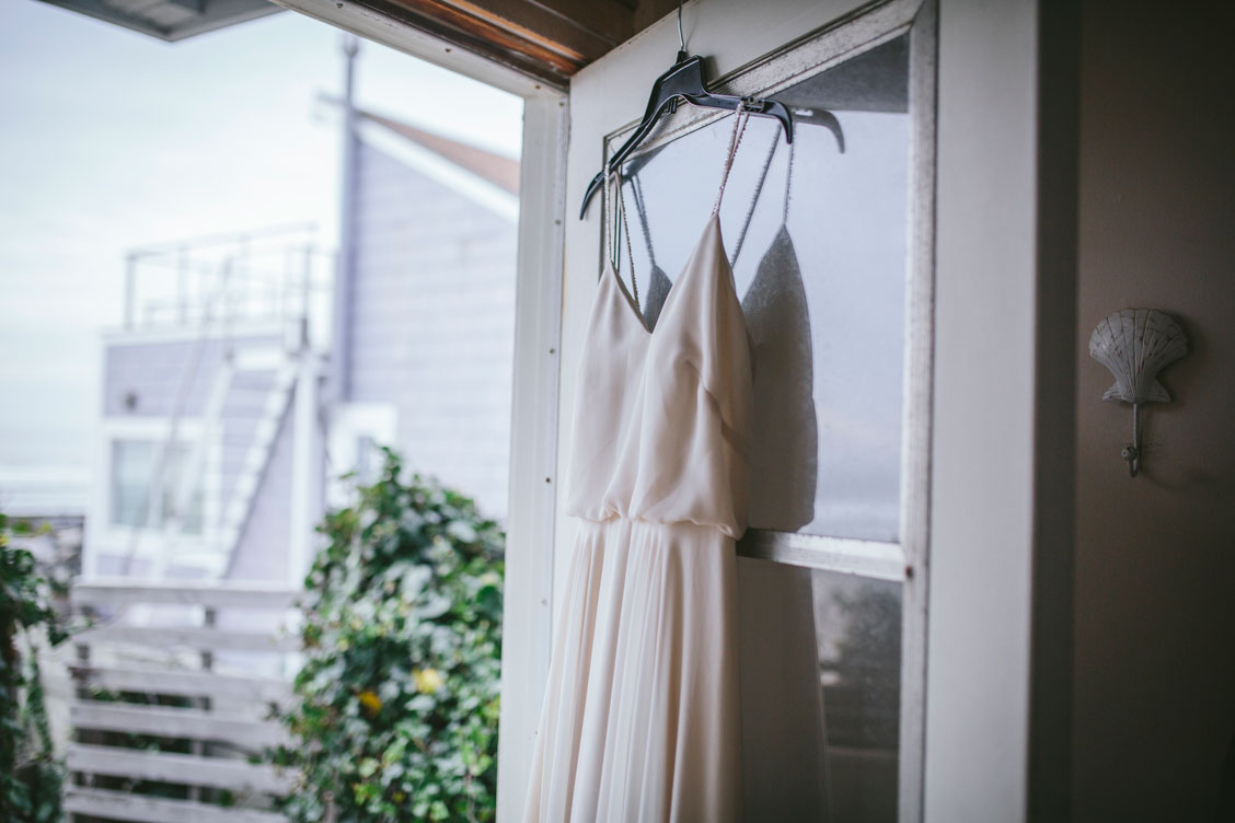 Wedding dress hanging before the ceremony by Becca Henry Photography