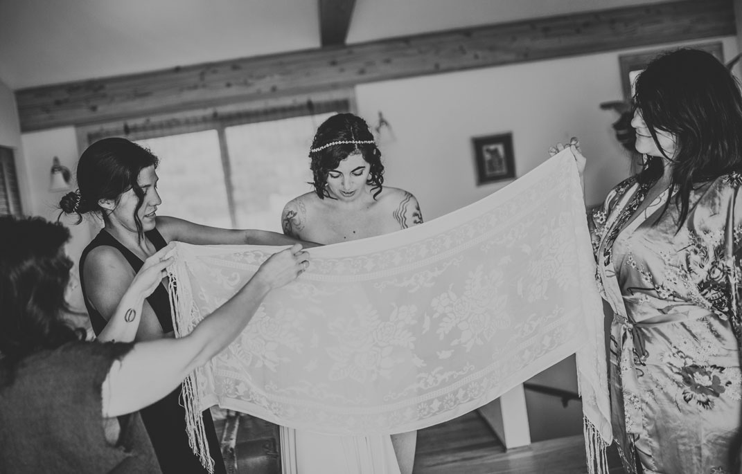 Bride putting on her dress at creative Stinson beach wedding by Becca Henry Photography