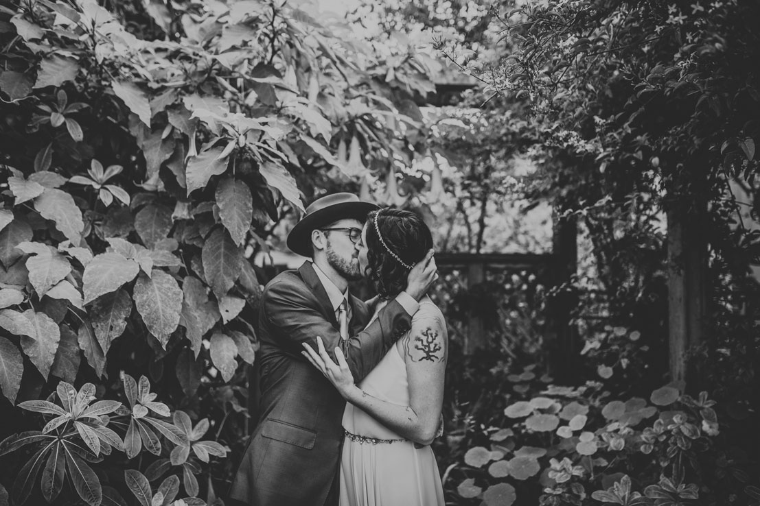 Sweet kiss in the garden at a Stinson Beach wedding by Becca Henry Photography