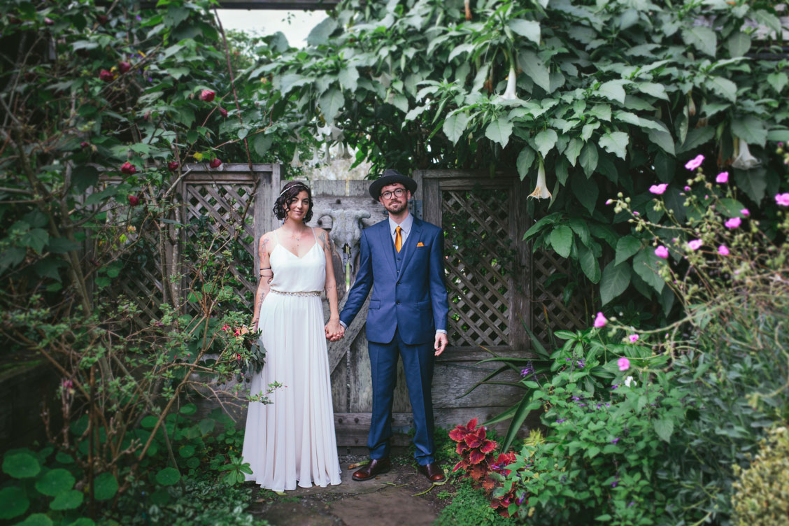 Portrait of wedding couple holding hands in a beautiful garden by Becca Henry Photography