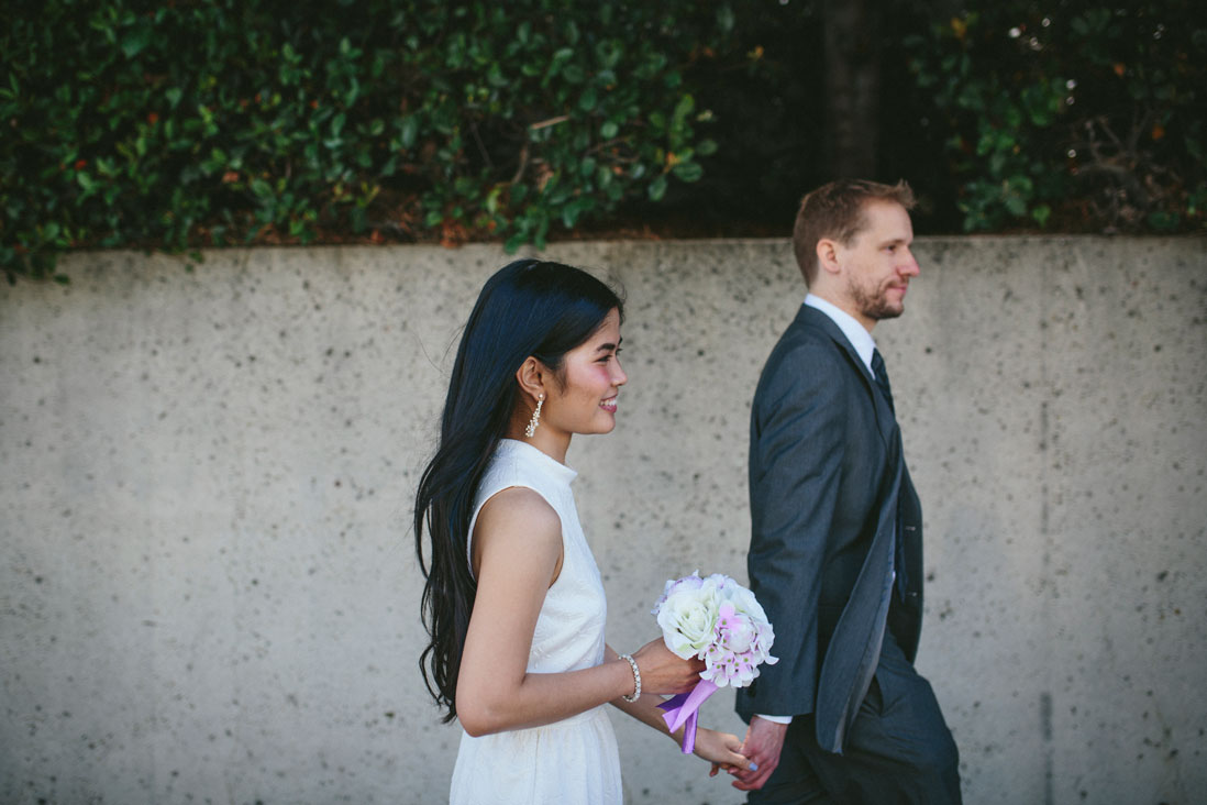 Oakland wedding couple walking in front of Oakland museum by Becca Henry Photography