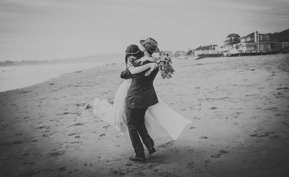 Groom twirls bride arounds on beach at Stinson Beach Wedding by Becca Henry Photography