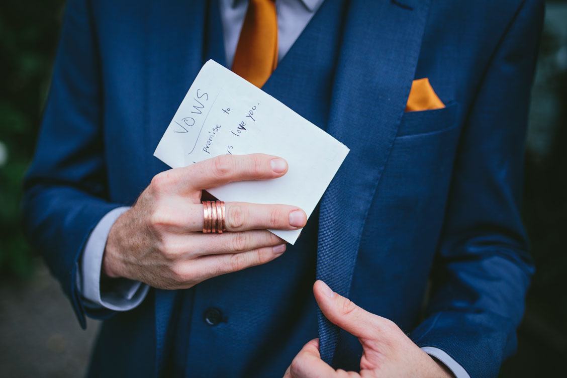 Groom with vows at creative wedding by Becca Henry Photography
