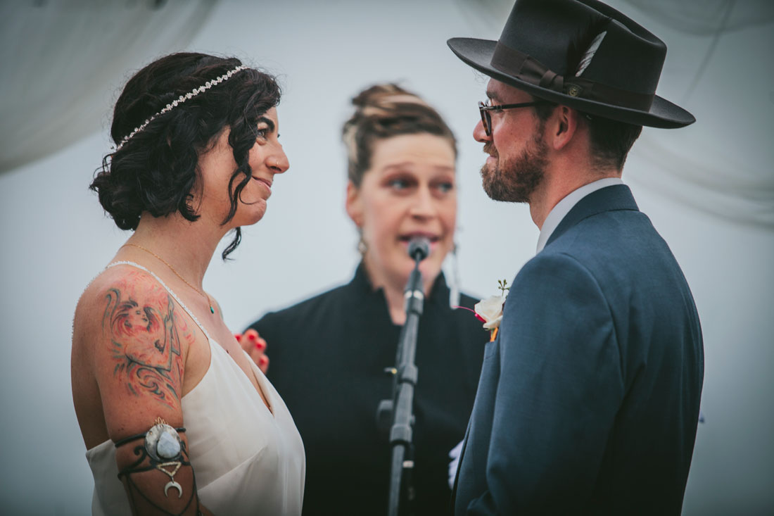 Couple looks at each other during beach ceremony at Stinson Beach Wedding by Becca Henry Photography