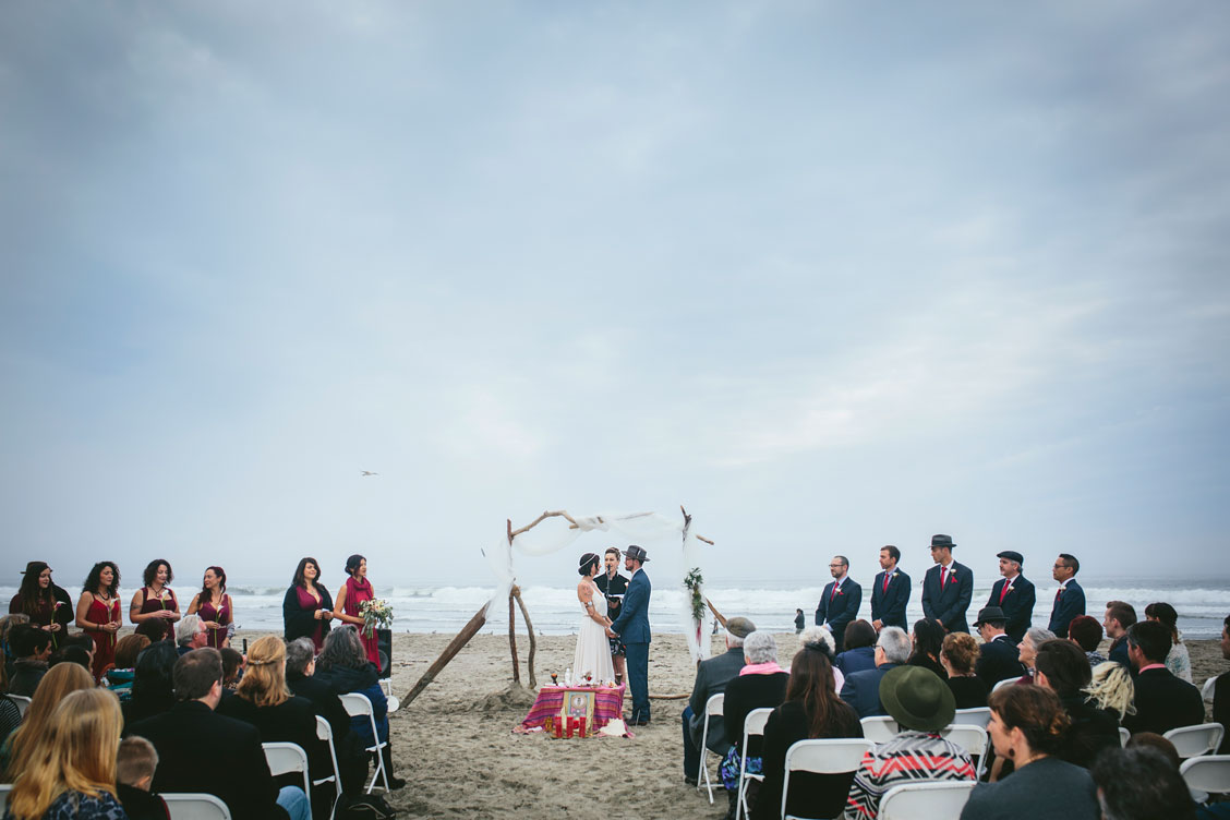 Reciting their vows on beach with audience watching on beach by Becca Henry Photography