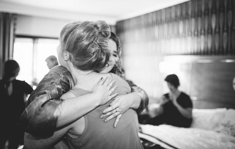 Friends embrace at Wedding at Waterfront Hotel in Oakland, CA by Becca Henry Photography