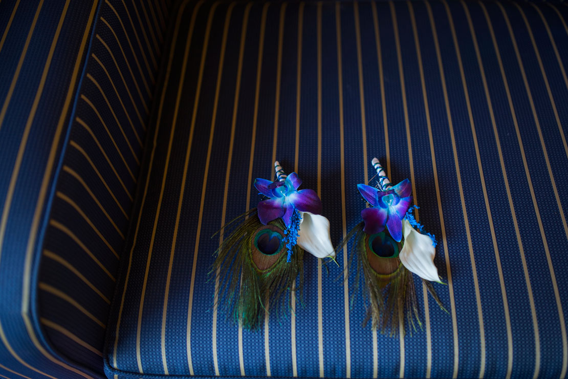 Wedding detail- groom's boutonniere with peacock feather and lily by Becca Henry Photography