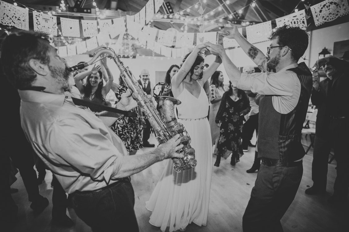 Bride and groom dancing to the band playing at Stinson Beach Community Center wedding reception by Becca Henry Photography