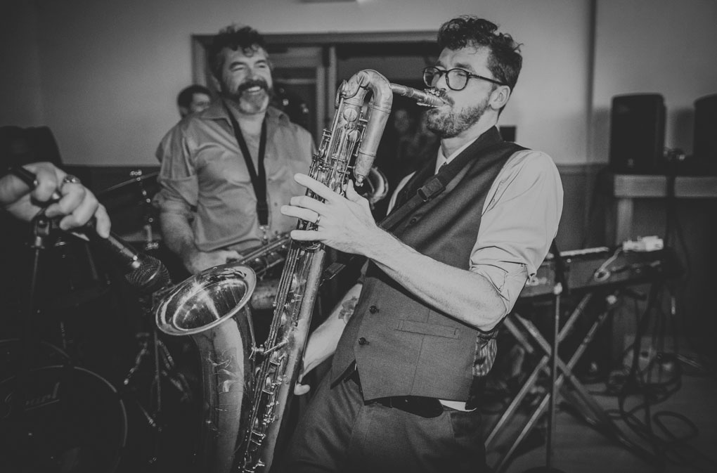Groom playing sax at his wedding reception by Becca Henry Photography