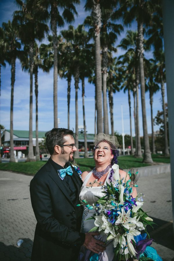 Creative wedding couple laughing in Jack London Square with palm trees in background by Becca Henry