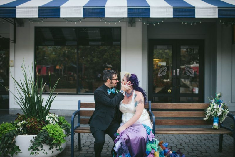 Alternative wedding- couple snuggles on bench in Jack London Square by Becca Henry Photography