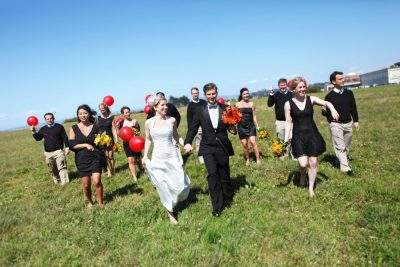 Wedding party in the Presidio with red balloons against a blue sky by Becca Henry Photography