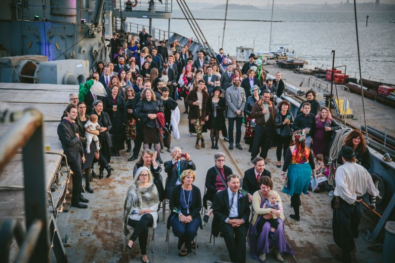 Wedding guests watching the ceremony on the SS Red Oak Victory by Becca Henry Photography.
