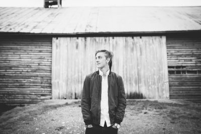 BW portrait of a young man in front of barn in Virginia by Becca Henry Photography