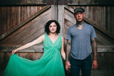 Couple in striking green dress and tats holding hands by Becca Henry Photography
