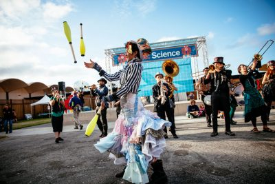 Performer juggling in front of a band of horn players at Maker Faire in San Mateo by Becca Henry Photography