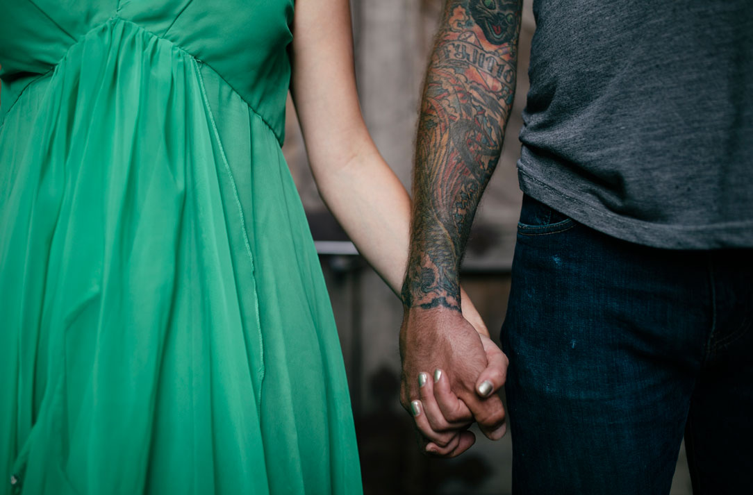 Holding hands with striking green dress, silver polish, and tattoos by Becca Henry