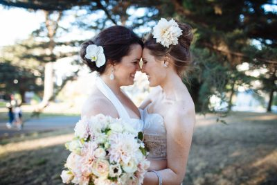 Two beautiful brides under the trees at Alamo Square in San Francisco by Becca Henry Photography