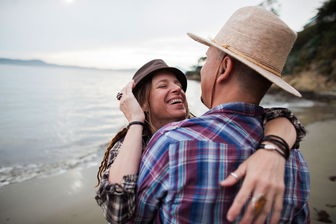 California casual engagement session- couple laughing and hugging on the beach by Becca Henry Photography