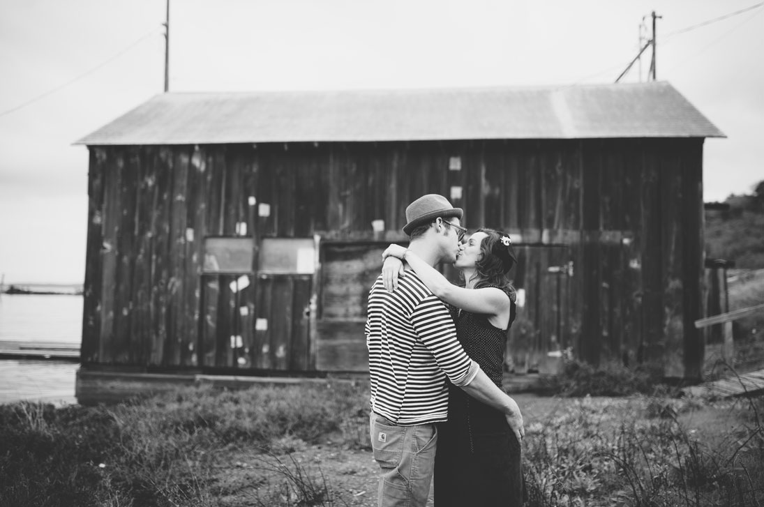 Bay Area engagement session- Kissing in front of rustic barn on the waterfront by Becca Henry Photography