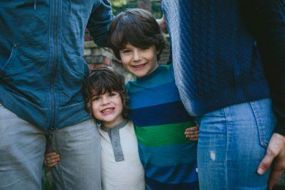 Two smiling boys arm in arm between their parents- Marin fun family photography by Becca Henry Photography
