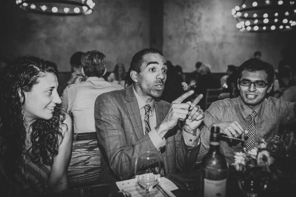 Wedding guest tells a good story at a wedding reception at El Camino, an Oakland venue by Becca Henry Photography