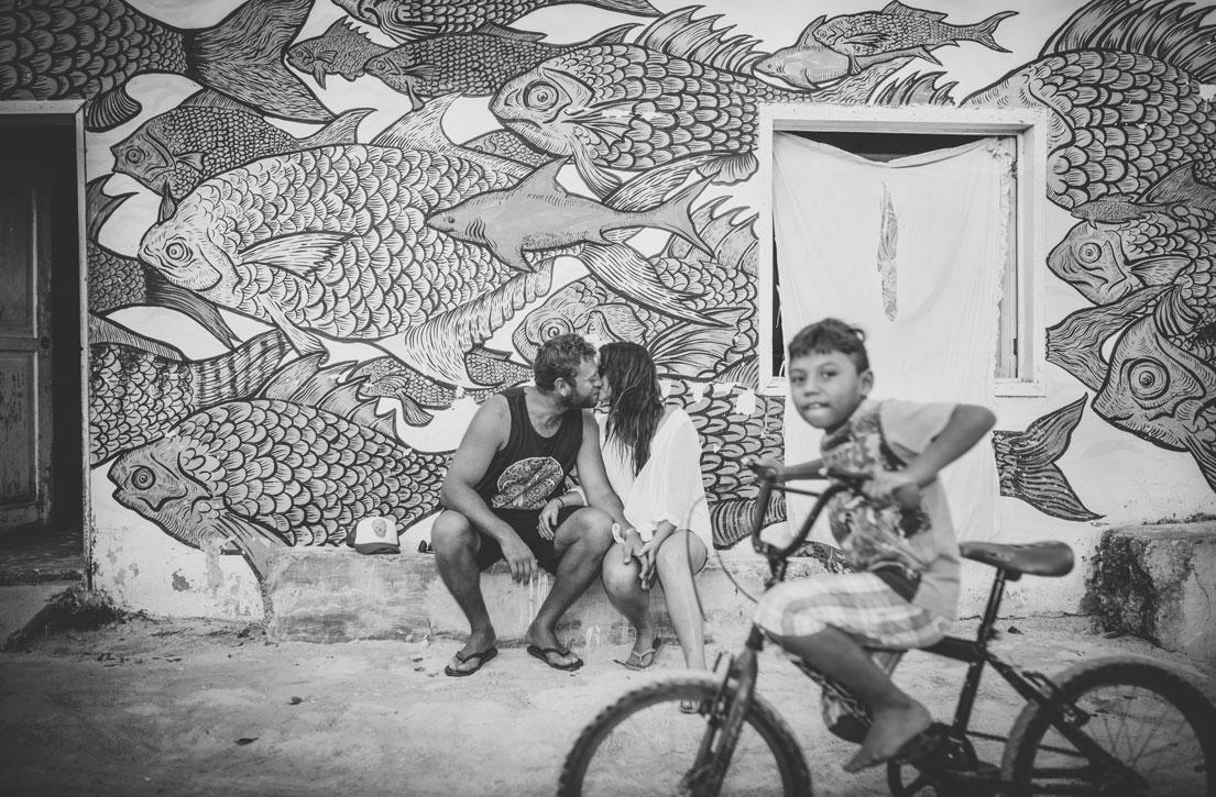 Kissing in front of awesome fish mural in Isla Holbox by Becca Henry
