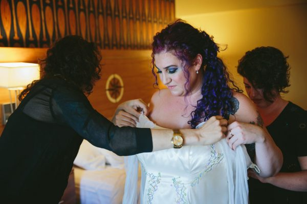 Bride putting on her dress with rad purple hair at Waterfront Hotel by Becca Henry Photography.