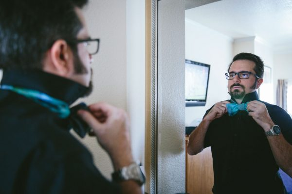 Groom straightening turquoise tie getting ready for the wedding by Becca Henry Photography