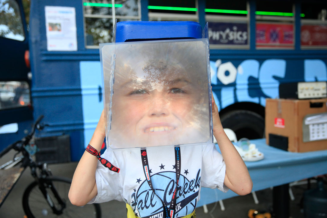 Kid demonstrates magnified face for Physics bus at Maker Faire in New York