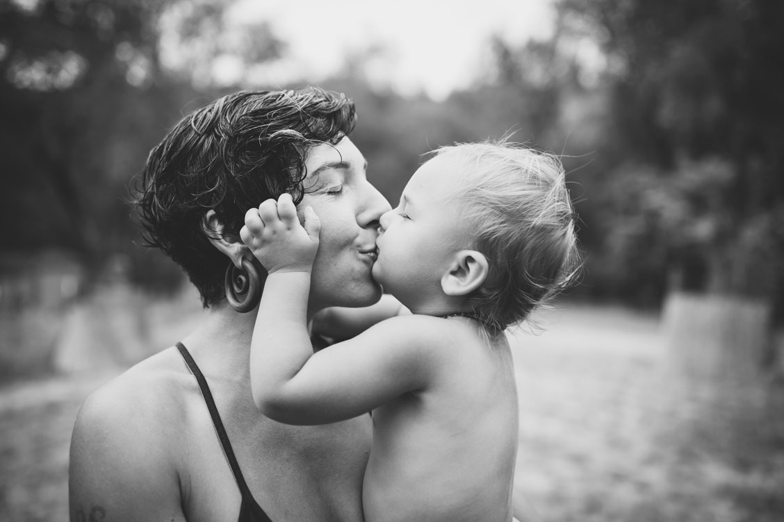 Black and white photo of 'lil one giving her mom a kiss by Becca Henry Photography