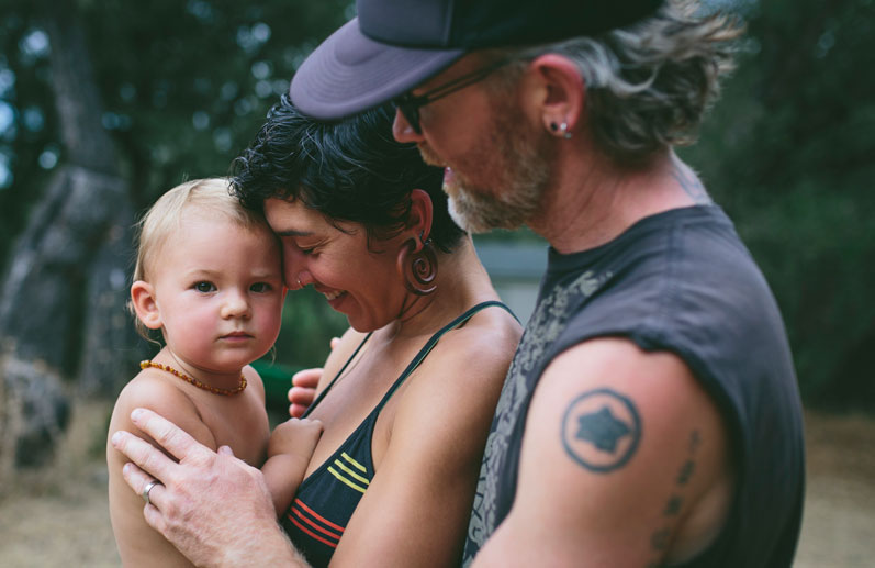 Mom and dad cuddling 'lil one outside by Becca Henry Photography