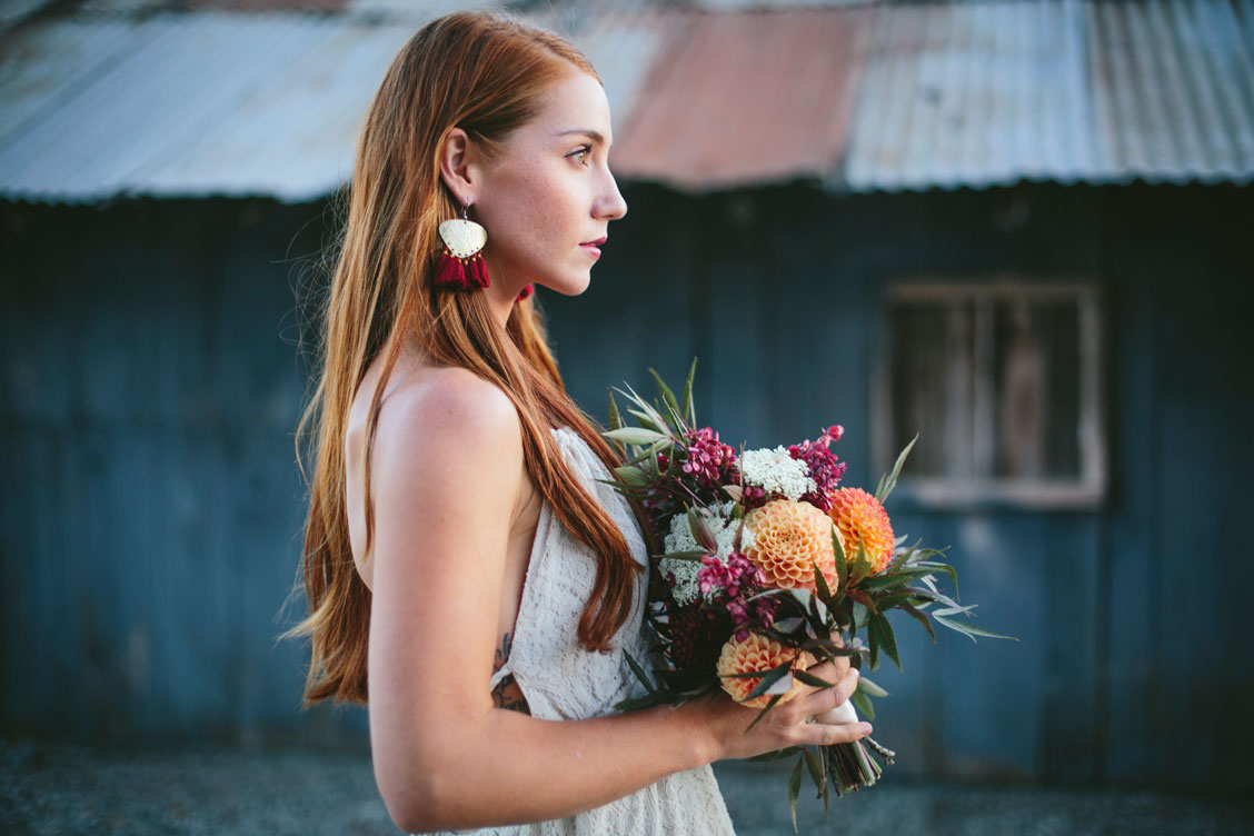 Bride in front of metal shed at Aztec Dahlia farm in Petaluma by Becca Henry Photography. Bouquet by Beijafloralbotanical.