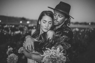 Couple in a field of flowers at Aztec Dahlia farm in Petaluma by Becca Henry Photography. Bouquet by Beijafloralbotanical.