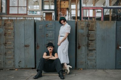 Editorial engagement photography Charlie Chaplin and ingenue by old school lockers at Ohmega Salvage by Becca Henry Photography