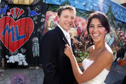 Urban SF wedding- laughing in front of mural in Clarion Alley by Becca Henry Photography