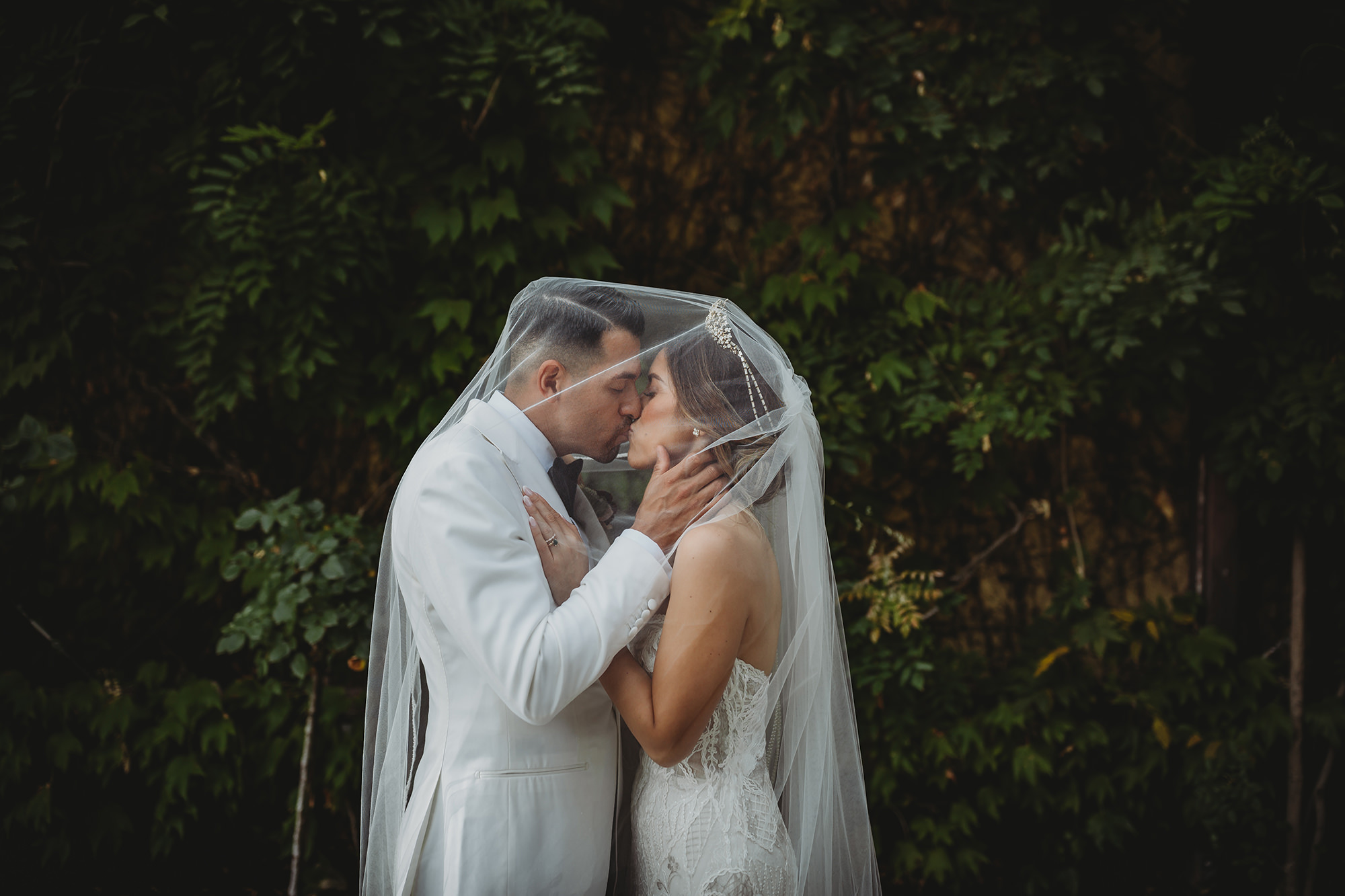 Bride and groom kiss under veil at the Harvest Inn Vineyard in St Helena