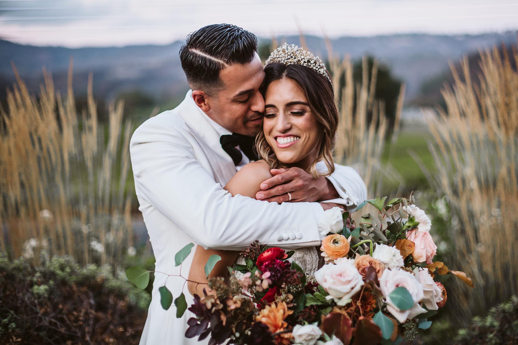 Groom sweetly embraces bride at St Helena wedding.