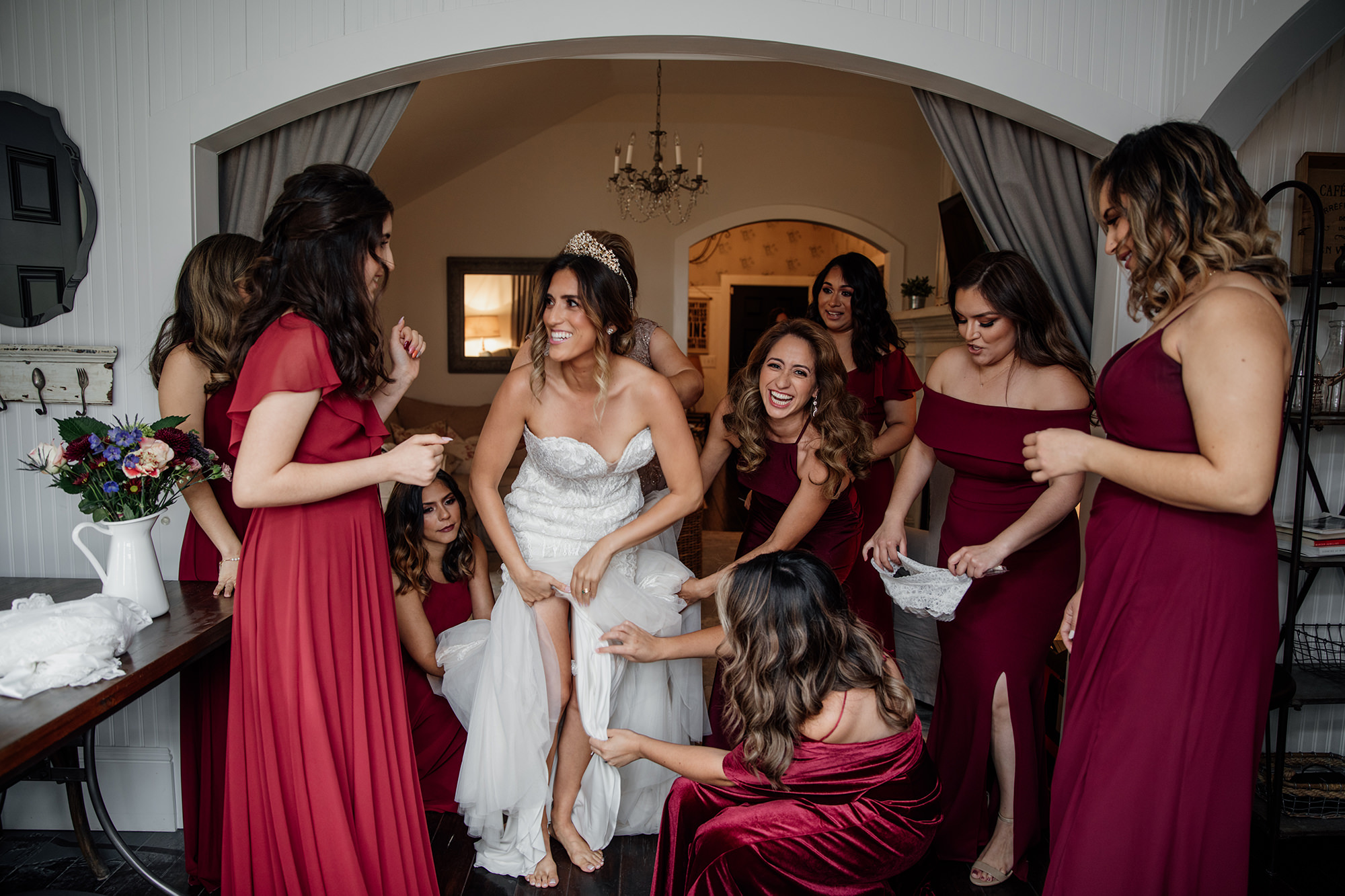 Bridesmaids helping bride with dress at St Helena wedding.
