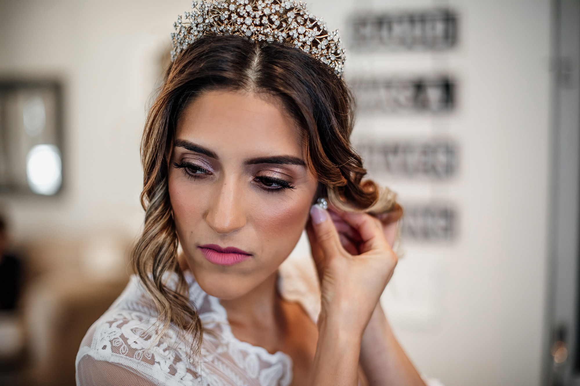 Bride with tiara putting on earring for Napa Valley Wedding.