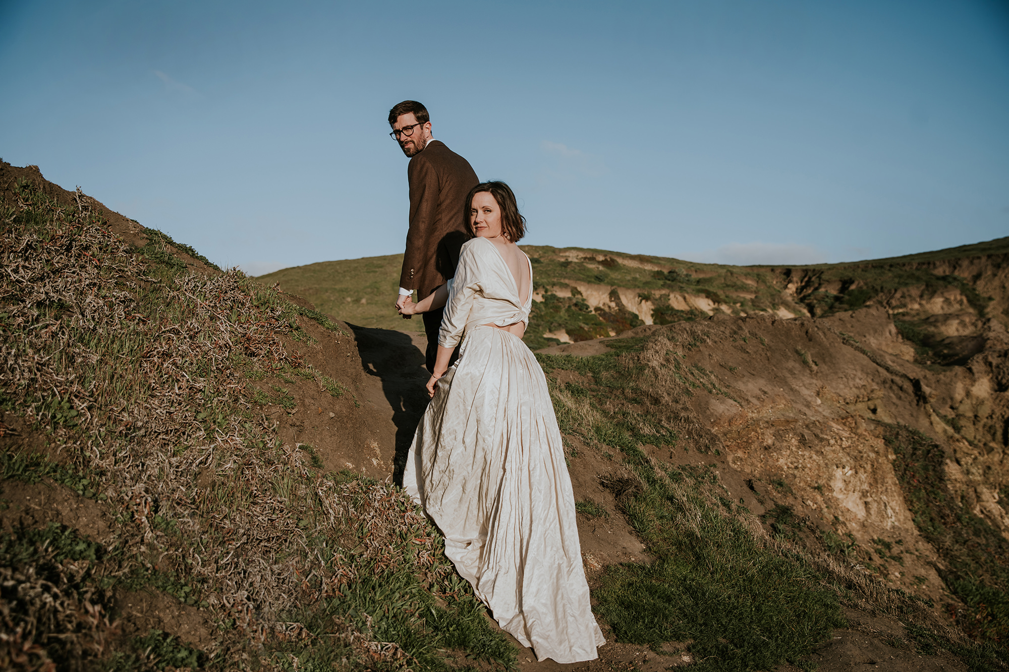 Climbing up the cliff side during their Point Reyes elopement.