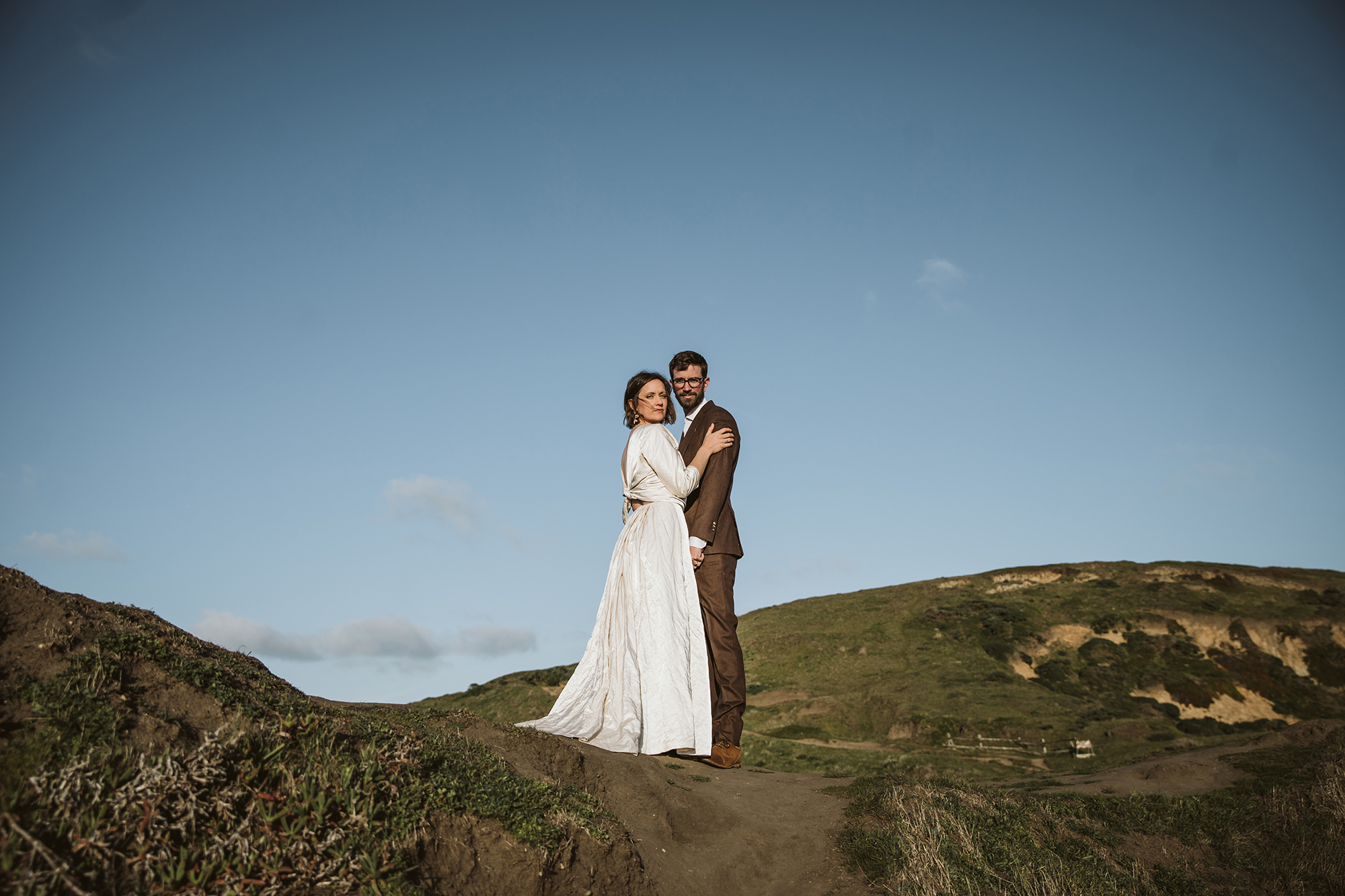 Bride and groom embrace at Chimney Rock at sunset for Point Reyes Elopement.