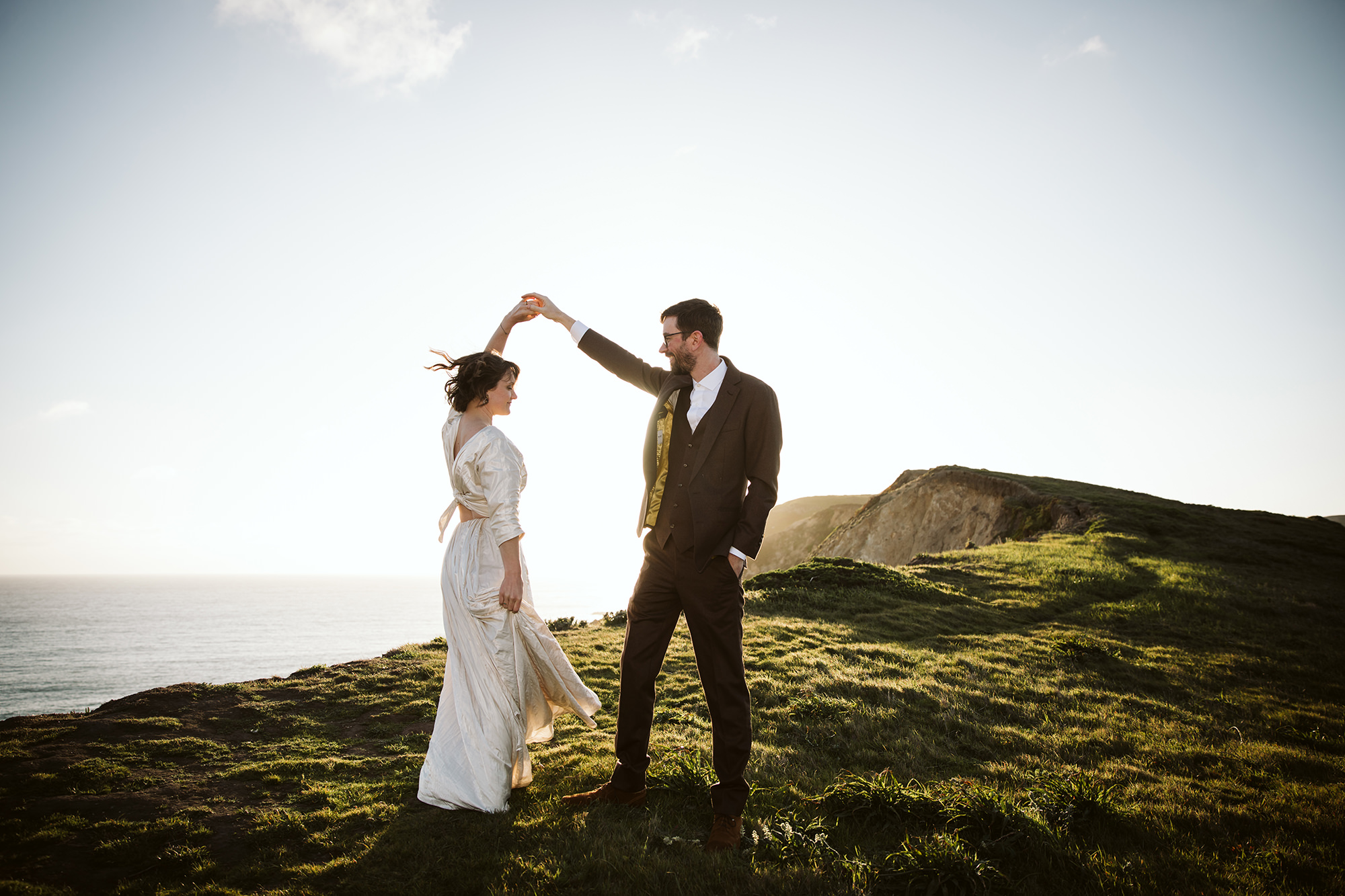 Groom twirling bride in the sunset during their Point Reyes elopement.