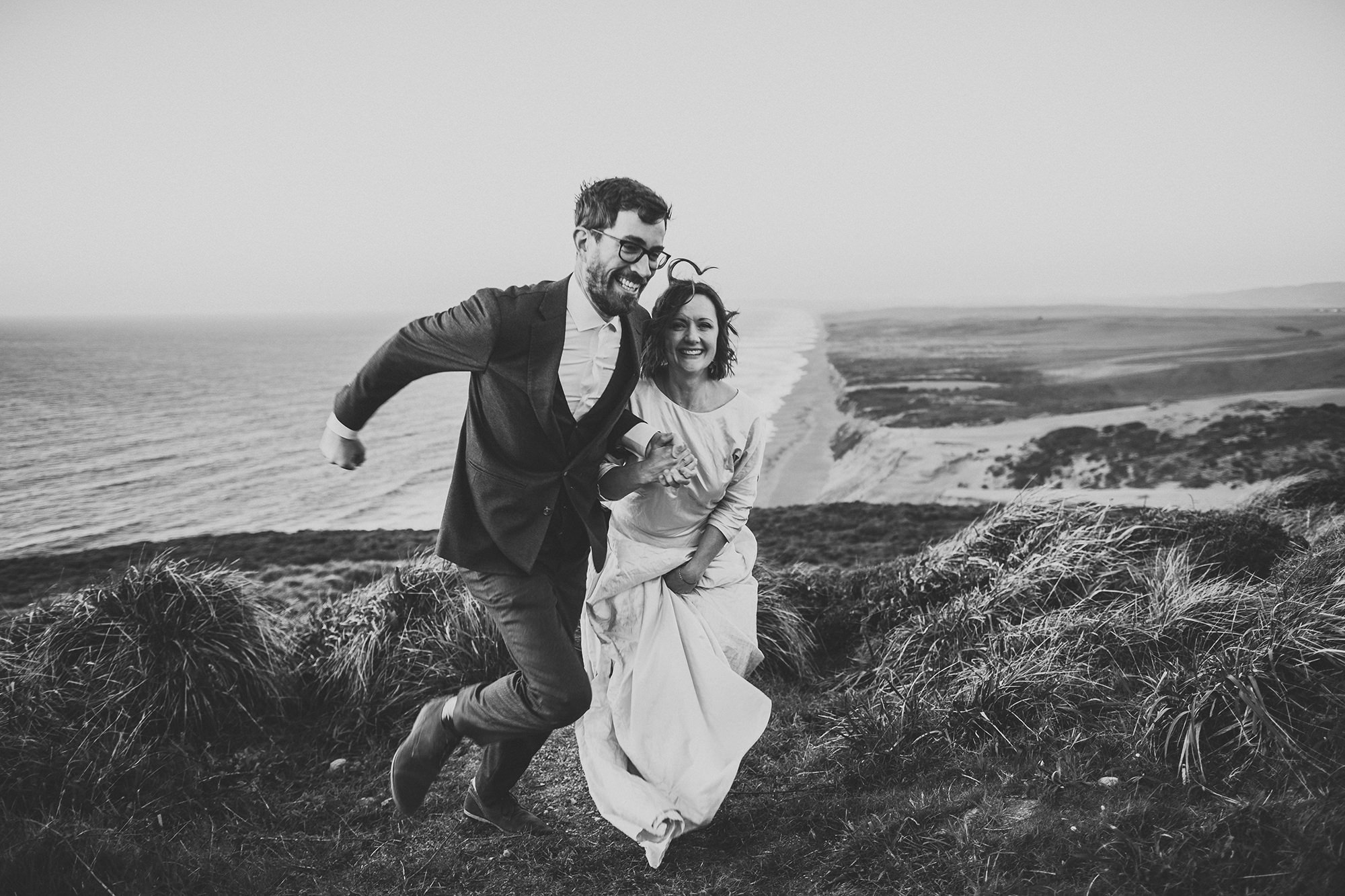 Bride and groom run to their car to get warm at the end of their Point Reyes elopement.