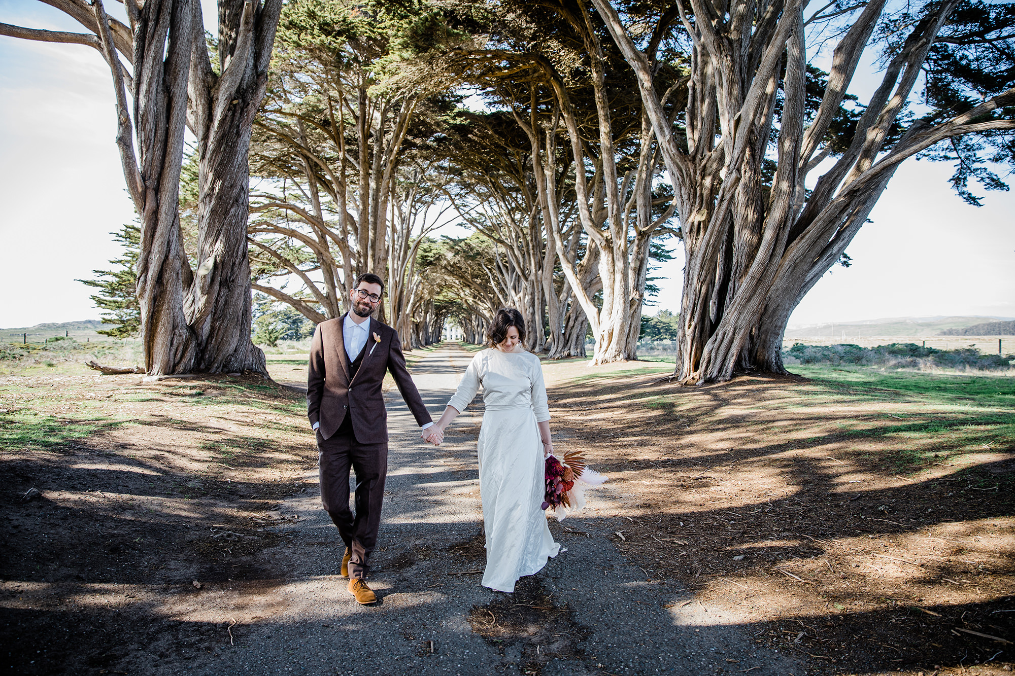Bride and groom holding holds at the Cypress Tree Tunnel for Point Reyes Elopement.