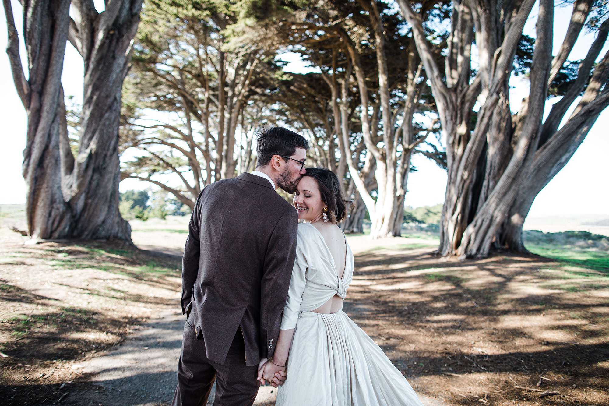 Groom sweetly kisses bride on forehead in the Cypress Tree Tunnel for Point Reyes Elopement.