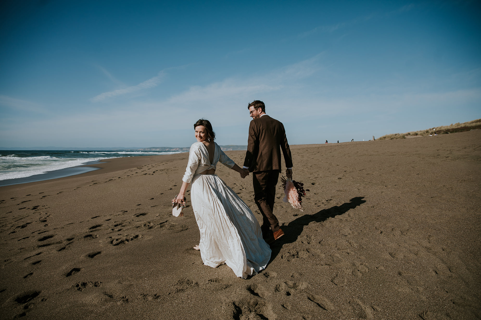 Bride and groom running along beach for Point Reyes Elopement