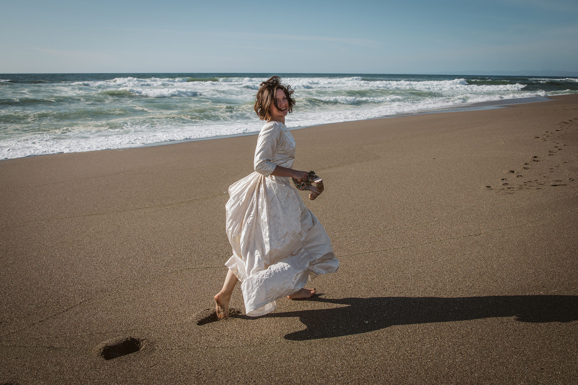 Bride playing on beach for Point Reyes Elopement.