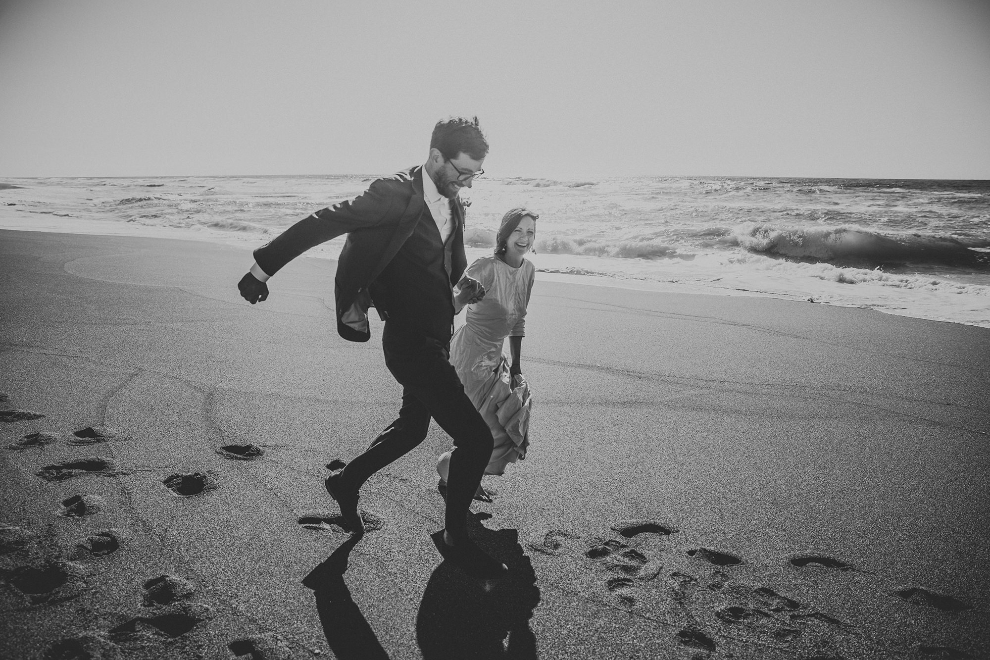 BW photo of bride and groom running on beach for California elopement