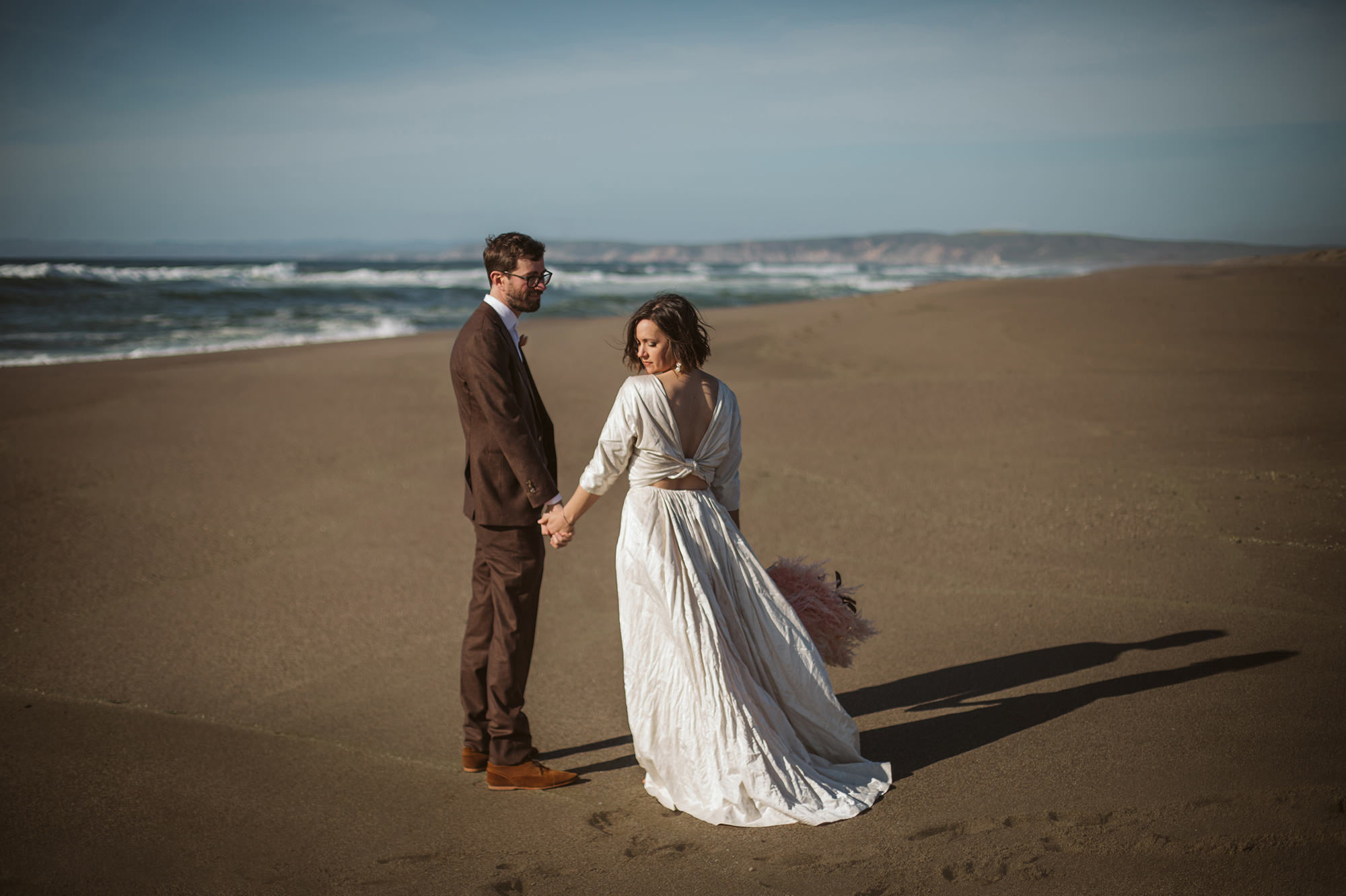 Bride and groom holding hands on beach for Northern California Elopement